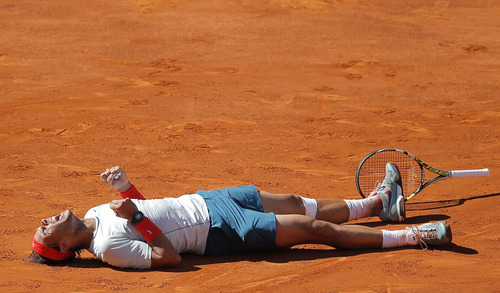 Rafael Nadal from Spain falls to the ground in celebration after winning the final of the Madrid Open tennis tournament against Stanislas Wawrinka from Switzerland, in Madrid Sunday, May 12, 2013. (AP Photo/Daniel Ochoa de Olza)
