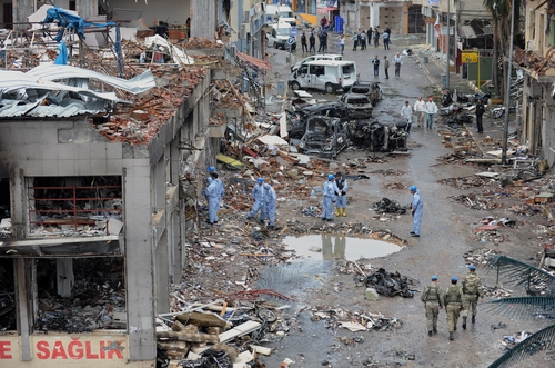 Police forensic officers work as army commandos patrol the area at the scene at one of the Saturday explosion sites that killed 46 and injured about 50 others, in Reyhanli, near Turkey's border with Syria, Sunday, May 12, 2013.  The bombings on Saturday marked the biggest incident of cross-border violence since the start of Syria's bloody civil war and has the raised fear of Turkey being pulled deeper into the conflict.(AP Photo)