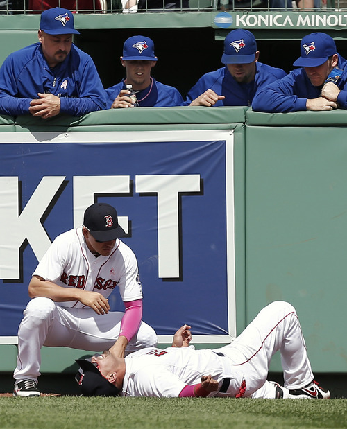 As Toronto Blue Jays, top, watch, Boston Red Sox right fielder Shane Victorino lies on the ground with teammate and center fielder Jacoby Ellsbury over him after crashing into the wall while trying to catch a two-run home run by Blue Jays' Emilio Bonifacio during the fourth inning of a baseball game at Fenway Park in Boston, Sunday, May 12, 2013. (AP Photo/Winslow Townson)