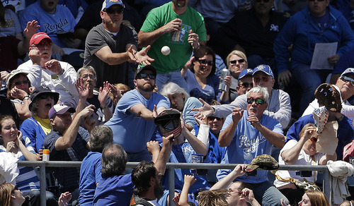 Fans vie for a foul ball hit by New York Yankees' Travis Hafner during the third inning of a baseball game against the Kansas City Royals, Sunday, May 12, 2013, in Kansas City, Mo. (AP Photo/Charlie Riedel)