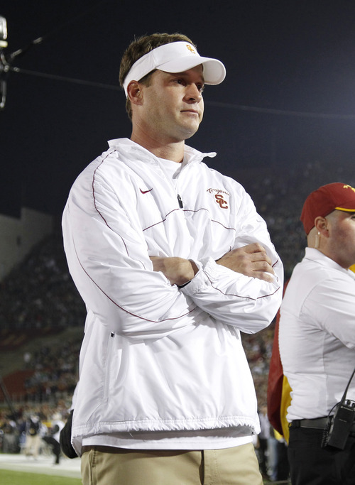FILE - In this Nov. 24, 2012 file photo, Southern California head coach Lane Kiffin looks on as senior quarterback Matt Barkley is introduced to the crowd during a ceremony for the seniors before an NCAA college football game against Notre Dame, in Los Angeles. Southern California is coming off a historically disappointing season that has put Kiffin in precarious situation heading into his fourth season as Trojans coach. The Trojans will have a new quarterback and are still dealing with a roster limited by NCAA sanctions. They won't enter the season No. 1 like last year. Expectations are far more modest, which both Kiffin and his boss, athletic director Pat Haden, say is a good thing. (AP Photo/Danny Moloshok, File)