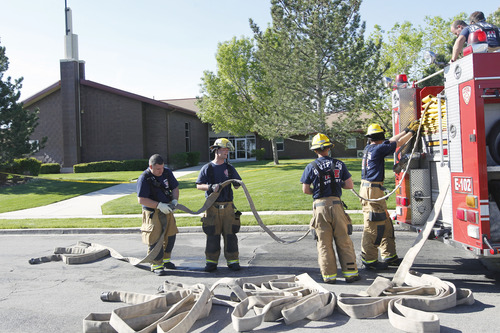 Al Hartmann  |  The Salt Lake Tribune Unified Fire Authority firefighters roll up the hoses after responding to a fire at an LDS Church building at 7525 W. 3735 South on Monday morning May 13.