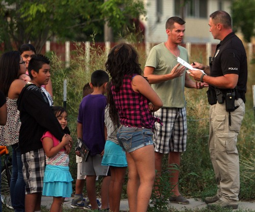 Kim Raff | The Salt Lake Tribune Police interview people as they investigate a fatal shooting on Grant Street in Salt Lake City, Utah on July 28, 2012.