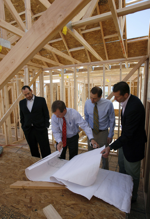Francisco Kjolseth  |  The Salt Lake Tribune Clark Ivory, second from left, CEO of Ivory Homes, the biggest homebuilder in Utah, overlooks plans on a new home being built in Stansbury Park along with Christopher Gamvroulas, president of Ivory development, CFO Rick Lifferth and Jim Seaberg, president of Ivory Commercial, from left. Ivory Homes has completed 15,000 houses over the years. It's been the top homebuilder in the state for at least 23 years and has been hugely influential in how homes in northern Utah look.
