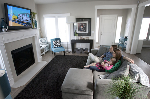 Steve Griffin | The Salt Lake Tribune   Tavnir and Hilary Carey watch television with their daughter, Gretel, in their new home in Daybreak in South Jordan, Utah Tuesday May 7, 2013. The family closed on their home at the end of March and by sheer coincidence, the sale happened to be the 15,000th home constructed by Ivory Homes.