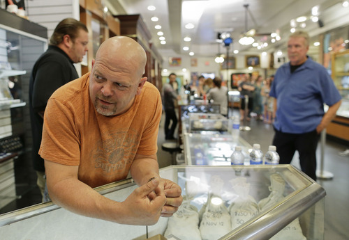 In this Wednesday, April 3, 2013, photo, Rick Harrison, owner of the Gold & Silver Pawn Shop waits as a camera crew prepares to shoot an episode of Pawn Stars at his shop in Las Vegas. Pawn sales at the shop, which is featured in the television reality show Pawn Stars, bring in about $20 million a year, up from the $4 million a year it made before the show aired. Turning small business owners into stars has become a winning formula for television producers, but the businesses featured in the shows are cashing in, too. Sales explode after just a few episodes have aired, transforming nearly unknown small businesses into household names.  (AP Photo/Julie Jacobson)