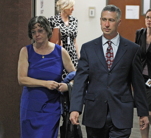 Arlene Holmes, left, mother of Aurora theater shooting suspect James Holmes, is escorted by a member of the defense team as she arrives for a hearing Monday, May 13, 2013, in Centennial, Colo., where her son asked a judge to enter a plea of not guilty by reason of insanity. (AP Photo/Brennan Linsley)