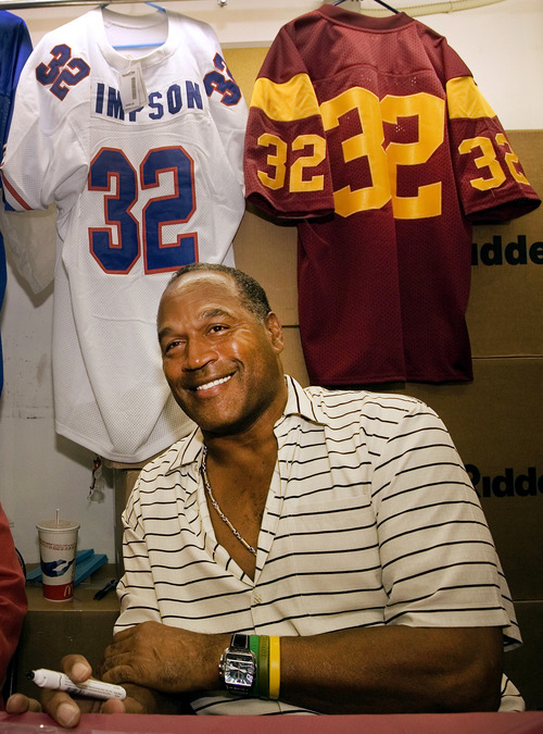"""FILE - In this Sept. 30, 2005 file photo, O.J. Simpson signs autographs during an event hosted by the """"NecroComicon'' horror convention in Northridge, Calif. The return of O.J. Simpson to a Las Vegas courtroom next Monday, May, 13,  will remind Americans of a tragedy that became a national obsession and in the process changed the country's attitude toward the justice system, the media and celebrity. The return of O.J. Simpson to a Las Vegas courtroom next Monday, May, 13,  will remind Americans of a tragedy that became a national obsession and in the process changed the country's attitude toward the justice system, the media and celebrity. (AP Photo/Damian Dovarganes, File)"""