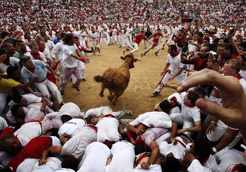 A cow jumps over revelers in a bullring during the second running of the bulls at the San Fermin fiestas, in Pamplona northern Spain, Sunday, July 8, 2012.(AP Photo/Ivan Aguinaga)