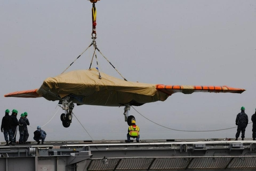 In this image provided by the U.S. Navy an X-47B Unmanned Combat Air System demonstrator is loaded onto the flight deck of the aircraft carrier USS George H.W. Bush on Monday May 6, 2013 in Norfolk, Va. The George H.W. Bush is scheduled to be the first aircraft carrier to catapult launch an unmanned aircraft from its flight deck on Tuesday May 14, 2013. (AP Photo/US Navy, Seaman Joshua P. Card)