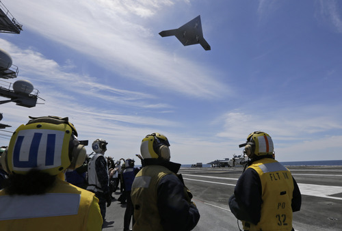 A Navy X-47B drone does a fly buy the nuclear powered aircraft carrier USS George H. W. Bush after it was launched off the coast of Virginia, Tuesday, May 14, 2013. (AP Photo/Steve Helber)