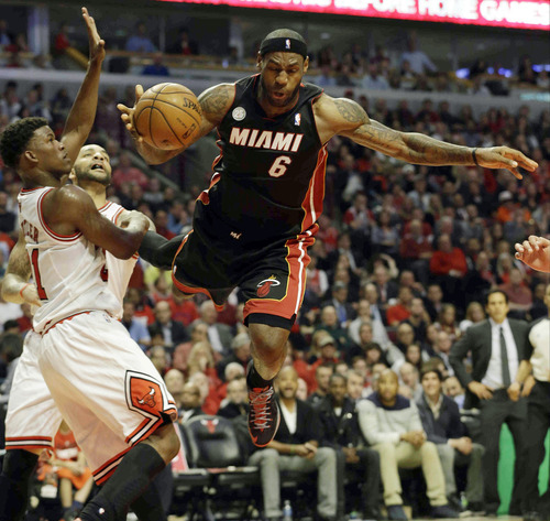Miami Heat forward LeBron James (6) goes after a rebound against Chicago Bulls forward Jimmy Butler, left, and Carlos Boozer during the first half of Game 4 of an NBA basketball playoffs Eastern Conference semifinal on Monday, May 13, 2013, in Chicago. (AP Photo/Nam Y. Huh)