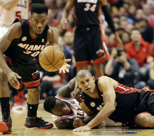 Miami Heat point guard Norris Cole (30) picks up a loose ball as Chicago Bulls guard Nate Robinson and Miami Heat forward Shane Battier, right, watch during the first half of Game 4 of an NBA basketball playoffs Eastern Conference semifinal on Monday, May 13, 2013, in Chicago. (AP Photo/Nam Y. Huh)
