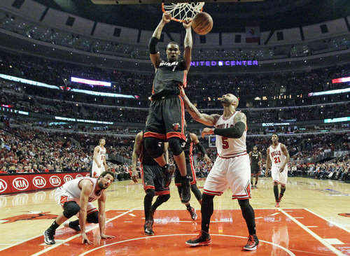 Miami Heat center Chris Bosh (1) dunks against Chicago Bulls forward Carlos Boozer (5) during the first half of Game 4 of an NBA basketball playoffs Eastern Conference semifinal on Monday, May 13, 2013, in Chicago. (AP Photo/Nam Y. Huh)