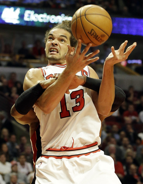Chicago Bulls center Joakim Noah (13) gets fouled by Miami Heat guard Dwyane Wade during the second half of Game 4 of an NBA basketball playoffs Eastern Conference semifinal on Monday, May 13, 2013, in Chicago. (AP Photo/Nam Y. Huh)