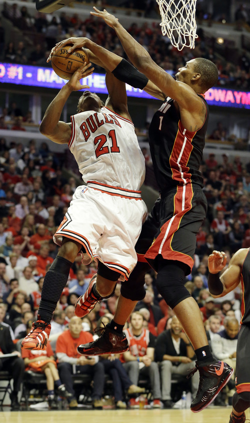 Miami Heat center Chris Bosh blocks a shot by Chicago Bulls forward Jimmy Butler (21) during the second half of Game 4 of an NBA basketball playoffs Eastern Conference semifinal on Monday, May 13, 2013, in Chicago. (AP Photo/Nam Y. Huh)