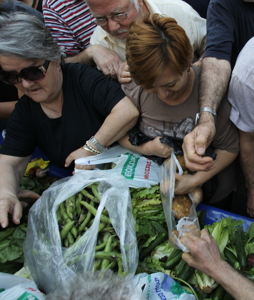 People push each other to get fresh produce as Greek market vendors hand out free food during a protest in Athens, Wednesday, May 15, 2013, as the union of Greek farmers markets went on strike Wednesday. Protesters set up stands and started distributing vegetables to a fast growing crowd. The market vendors are the latest professional group in Greece to protest a sweeping market liberalization drive demanded by rescue creditors, and timed their protest to coincide with draft legislation due to be voted in parliament to implement the new guidelines.(AP Photo/Thanassis Stavrakis)