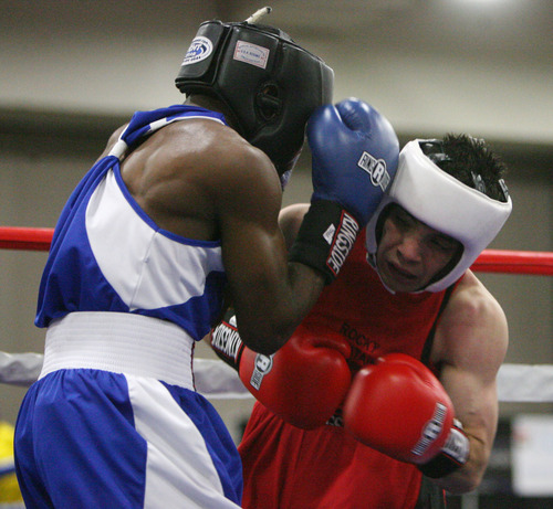 Steve Griffin | The Salt Lake Tribune   Utah's Isaac Aguliar, right, battles Sharone Carter, of St. Louis, during Golden Gloves boxing tournament at the Salt Palace Convention Center in Salt Lake City, Utah Wednesday May 15, 2013. Aguliar defeated Carter.