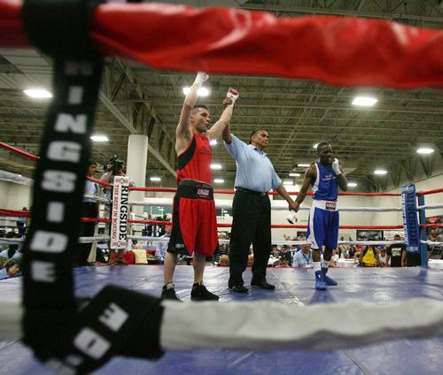 Steve Griffin | The Salt Lake Tribune   Utah's Isaac Aguliar's hand is raised into the air, by the referee, as he defeats Sharone Carter, of St. Louis, during Golden Gloves boxing tournament at the Salt Palace Convention Center in Salt Lake City, Utah Wednesday May 15, 2013.