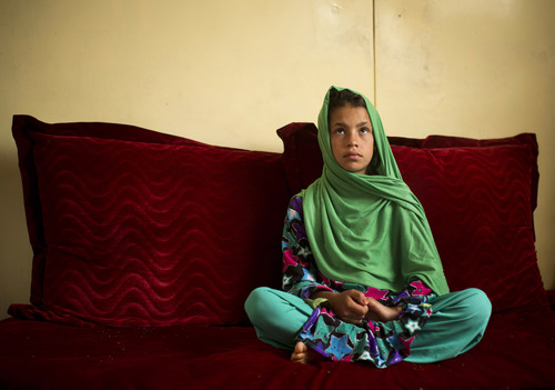 """Zardana, 11, sits as she talks in Kandahar, Afghanistan on Monday, April 22, 2013 about pre-dawn March 11, 2012 when she says a U.S. soldier burst into her family's home. Zardana said her visiting cousin saw the soldier chasing them and ran to help, but he was shot and killed. """"We couldn't stop. We just wanted somewhere to hide. I was holding on to my grandmother and we ran to our neighbors."""" (AP Photo/Anja Niedringhaus)"""