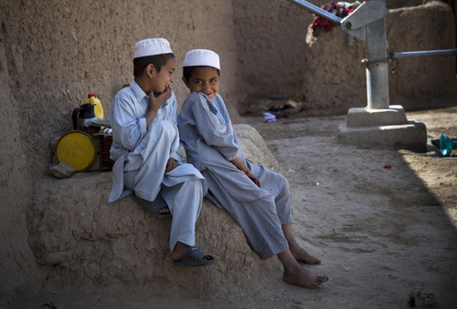 Naseebullah, left, and Azatullah sit together in the outskirts of Kandahar, Afghanistan on Saturday, April 20, 2013. In an interview, their mother, Masooma, recounted the events of a pre-dawn last year when a U.S. soldier rampaged through two villages killing 16 people, including their father. (AP Photo/Anja Niedringhaus)