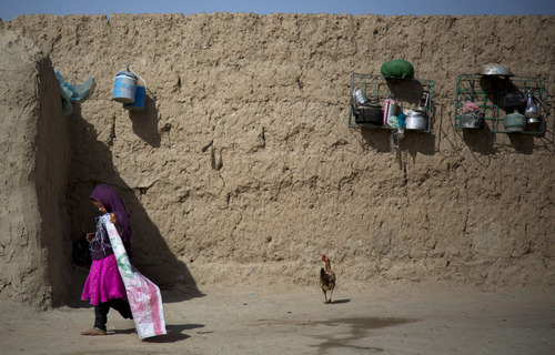 A girl plays at her home on the outskirts of Kandahar, Afghanistan on Saturday, April 20, 2013. In an interview, her aunt, Masooma, recounted the events of a pre-dawn attack last year when she says a U.S. soldier rampaged through two villages killing 16 people, including her husband. (AP Photo/Anja Niedringhaus)
