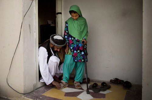 Eleven-year-old Zardana, is helped with her sandals by her father Samiullah after an interview in Kandahar, Afghanistan on Monday, April 22, 2013. She recounted the night of March 11, 2012 when she says a U.S. soldier attacked their family home, shooting her in the head and killed 11 relatives. She suffered nerve damage on her left side and has to walk with a cane. Her hand is too weak to hold anything heavy. (AP Photo/Anja Niedringhaus)