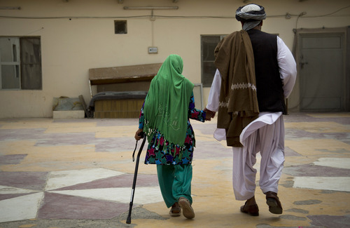 Zardana, 11, holds the hand of her father, Samiullah, after an interview in Kandahar, Afghanistan on Monday, April 22, 2013. Surviving family members said a U.S. soldier attacked their home on March 11, 2012, shooting her in the head. Zardana spent about two months recovering at the Kandahar Air Base hospital and three more at a naval hospital in San Diego receiving rehabilitation therapy, accompanied by her father, Samiullah. (AP Photo/Anja Niedringhaus)