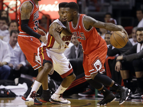 Chicago Bulls' Nate Robinson, right, drives to the basket as Miami Heat's Norris Cole, center, defends during the first half of Game 5 of an NBA basketball Eastern Conference semifinal, Wednesday, May 15, 2013, in Miami. (AP Photo/Wilfredo Lee)