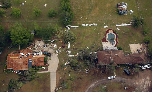 This aerial photo shows homes that were damaged by Wednesday's tornado in Cleburne, Texas on Thursday, May 16, 2013.  Ten tornadoes touched down in several small communities in Texas overnight, leaving at least six people dead, dozens injured and hundreds homeless. Emergency responders were still searching for missing people Thursday afternoon.  (AP Photo/The Dallas Morning News, G.J.McCarthy)  MANDATORY CREDIT; MAGS OUT; TV OUT; INTERNET USE BY AP MEMBERS ONLY; NO SALES