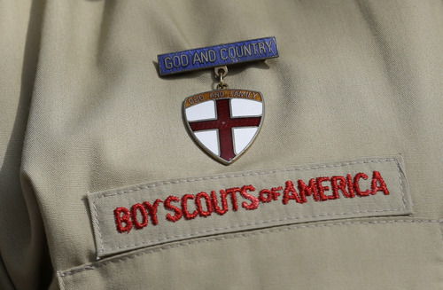 This photo taken  Monday, Feb. 4, 2013, shows a close up detail of a Boy Scout uniform worn by Brad Hankins, a campaign director for Scouts for Equality, as he responds questions during a news conference in front of the Boy Scouts of America headquarters in Irving, Texas.  (AP Photo/Tony Gutierrez)