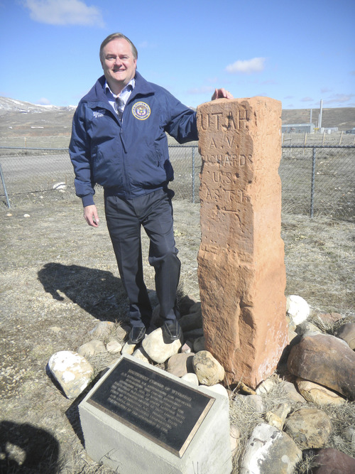 Mike Mower, deputy chief of staff for Gov. Gary Herbert, examines an old survey marker separating Utah and Wyoming. (Tom Wharton Photo).