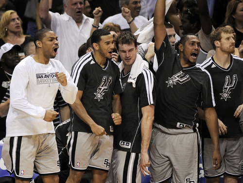 The San Antonio Spurs bench celebrates a basket in the closing seconds of Game 5 of the Western Conference semifinal NBA basketball playoff series against the Golden State Warriors, Tuesday, May 14, 2013, in San Antonio. San Antonio won 109-91. (AP Photo/Darren Abate)