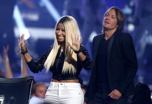 "Judges Nicki Minaj, left, and Keith Urban greet the audience at the ""American Idol"" finale at the Nokia Theatre at L.A. Live on Thursday, May 16, 2013, in Los Angeles. (Photo by Matt Sayles/Invision/AP)"
