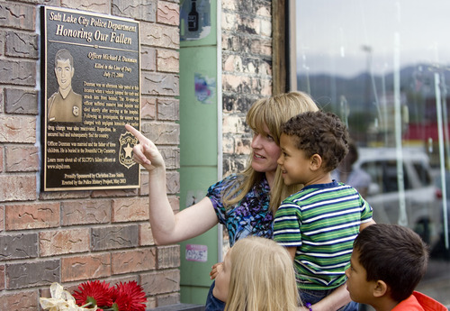 Kim Raff  |  The Salt Lake Tribune Sandi Bromley and Bronson Bromley look at a plaque in memory of Sandi's husband Officer Michael Dunman, who was killed while on duty 13 years ago, during the Salt Lake Police Department's dedication outside of Piper Down Pub in Salt Lake City on Friday.