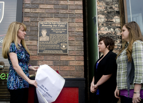 Kim Raff  |  The Salt Lake Tribune Sandi Bromley, left, and daughters Karissa Dunman and Kaitlyn Dunman unveil a plaque in memory of their fallen husband and father, Salt Lake City police Officer Michael Dunman, who was killed while on duty 13 years ago, outside Piper Down Pub in Salt Lake City on May 17, 2013.