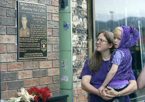 Kim Raff  |  The Salt Lake Tribune Sherri and Amanda Stringham look at a plaque in memory of Sherri's brother-in-law Officer Michael Dunman, who was killed while on duty 13 years ago, during the Salt Lake Police Department's dedication ceremony outside Piper Down Pub in Salt Lake City on May 17, 2013.