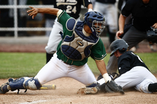 Chris Detrick  |  The Salt Lake Tribune Desert Hills' Ty Rutledge (31) slides safely into home base past Snow Canyon's Brady Sargent (25) during the game at Brent Brown Ballpark at Utah Valley University Friday May 17, 2013. Desert Hills defeated Snow Canyon 5-4.