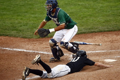 Chris Detrick  |  The Salt Lake Tribune Desert Hills' Andrew Basile (10) slides safely into home base past Snow Canyon's Brady Sargent (25) during the game at Brent Brown Ballpark at Utah Valley University Friday May 17, 2013. Desert Hills defeated Snow Canyon 5-4.