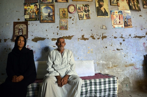 The parents of 24-year-old school teacher Dimyana Abdel-Nour, who is accused of insulting Islam while teaching fourth graders history of religions, pose for a photograph in their home in southern Egypt's ancient city of Luxor, Egypt, Thursday, May 16, 2013. Freed on Tuesday on a 20,000-pound (nearly 3,000 dollars) bail after nearly a week in detention, Abdel-Nour is due to stand trial later this month. Criminalizing blasphemy was enshrined in the country's new Islamist-backed constitution adopted in December. (AP Photo/Ibrahim Zayed)
