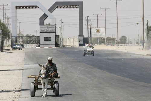 In this Monday, Aug. 6, 2012 file photo, a Palestinian man rides a donkey cart outside the Rafah border crossing between southern Gaza Strip and Egypt. Dozens of disgruntled border policemen forced the closure on Friday, May 17, 2013, of the Rafah border crossing into the Gaza strip to protest the abduction of their colleagues by suspected militants, underscoring the country's lawlessness and its crisis of authority two years since the uprising that toppled Hosni Mubarak. At Rafah terminal, one of the protesting policemen said that they will keep it closed until their colleagues are freed. (AP Photo/Hatem Moussa, File)