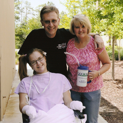 FILE - In this Saturday, June 23 2012 file photo provided by the Copeland family, Aimee Copeland, left, poses with her parents, Andy and Donna Copeland, outside Doctors Hospital in Augusta, Ga. Aimee Copeland, who lost both hands, her left leg and right foot after contracting a flesh-eating disease, was on her way back from Ohio Friday, May 17, 2013 after being fitted with prosthetic hands. (AP Photo/Copeland Family, File)