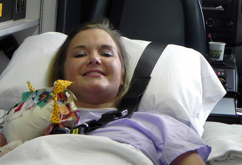 In this Monday, July 2, 2012 file photo provided by Andy Copeland, Aimee Copeland smiles as she leaves a hospital in Augusta, Ga., headed for an inpatient rehabilitation clinic. Copeland, who lost both hands, her left leg and right foot after contracting a flesh-eating disease, was on her way back from Ohio, on Friday, May 17, 2013 after being fitted with prosthetic hands. (AP Photo/Courtesy of Andy Copeland, File)