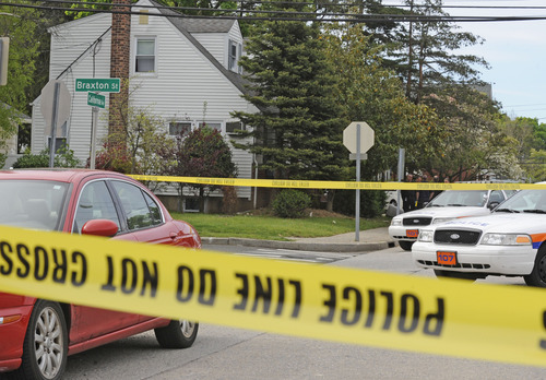 Officers continue working the scene at the house, left, where a Hofstra University student and an armed intruder were killed during an overnight break-in next to the campus, Friday, May 17, 2013, in Uniondale, N.Y. (AP Photo/ Louis Lanzano)