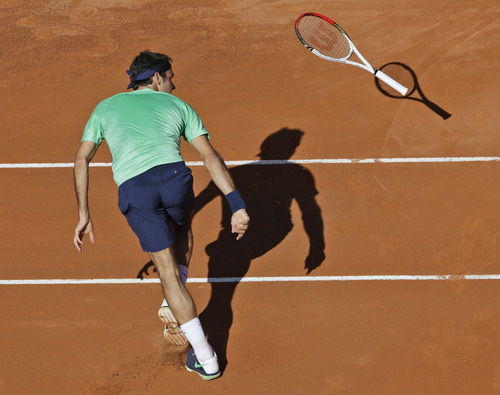 Roger Federer of Switzerland loses his tennis racket during the final match against Spain's Rafael Nadal,  at the Italian Open tennis tournament in Rome, Sunday, May 19, 2013.  Nadal won 6-1, 6-3. (AP Photo/Alessandra Tarantino)