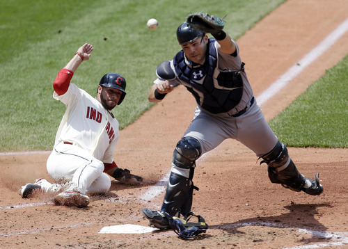 Cleveland Indians' Mike Aviles, left, scores as Seattle Mariners catcher Jesus Montero cannot hold on to the ball in the fourth inning of a baseball game on Sunday, May 19, 2013, in Cleveland. (AP Photo/Tony Dejak)