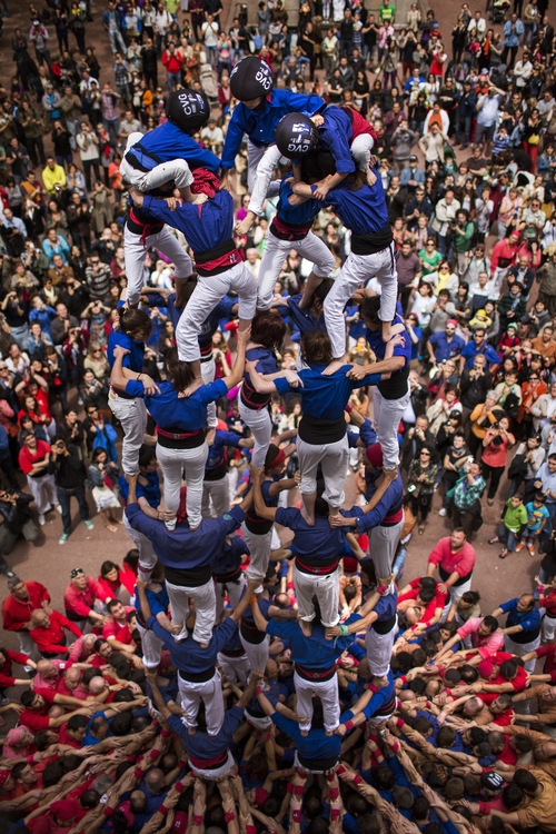 "Members of the Castellers ""Vila de Gracia"" form their famous human tower called ""castell"" in the Barcelona neighborhood of Gracia, Catalonia, Spain on Sunday May 19, 2013. A ""castell"" is a human tower traditionally built during festivals in many places in Catalonia. At these festivals, several ""colles"" or teams compete to build the most impressive towers they can. (AP Photo/Emilio Morenatti)"