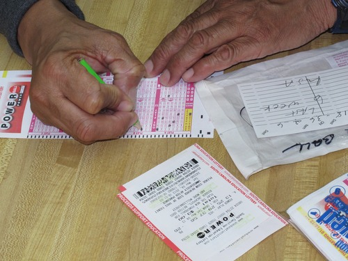 Armous Peterson fills out his slip for the Powerball lottery at Jimmy's Mart on Saturday, May 18, 2013, in Columbia, S.C. Peterson keeps track of what numbers he plays from week to week. (AP Photo/Jeffrey Collins)