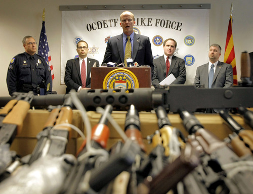 """In this Tuesday, Jan. 25, 2011 picture, Bill Newell, special agent in charge of ATF Phoenix, speaks behind a cache of seized weapons in Phoenix. The ATF is under fire over a Phoenix-based gun-trafficking investigation called """"Fast and Furious,"""" in which agents allowed hundreds of guns into the hands of straw purchasers in hopes of making a bigger case. Two of those weapons were found in December 2010 at the fatal shooting of an U.S. Border Patrol agent, igniting a scandal that has resulted in a congressional investigation and review by the Justice Department's Office of Inspector General. (AP Photo/Matt York)"""