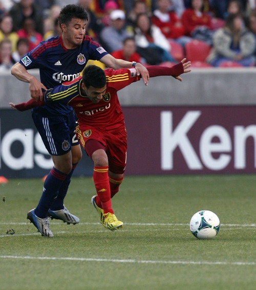 Kim Raff  |  The Salt Lake Tribune (right) Real Salt Lake midfielder Javier Morales (11) is held back by (left) Chivas USA midfielder Carlos Alvarez (20) as he tries to get to the ball during the first half at at Rio Tinto Stadium in Sandy on April 20, 2013. Real went on to win the game 1-0.